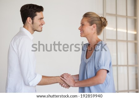 Casual business woman shaking hands with man in the office