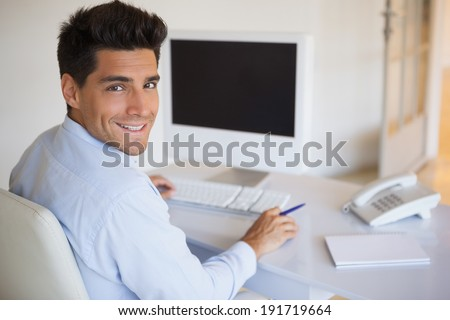 Casual businessman at desk smiling at camera in his office - stock photo