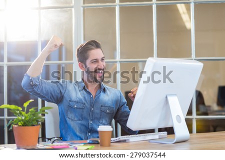 Casual businessman cheering in front of his computer in the office - stock photo