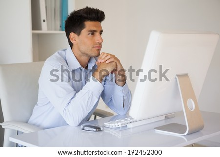 Casual businessman concentrating at his desk in his office