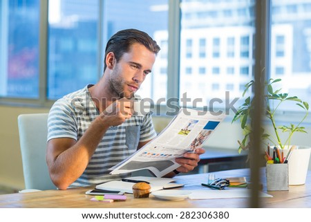 Casual businessman drinking coffee and reading magazine at his desk in the office - stock photo