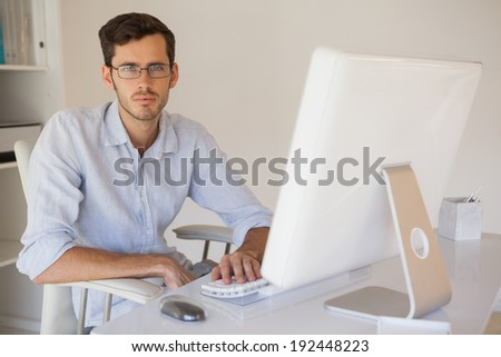 Casual businessman frowning at camera at his desk in his office