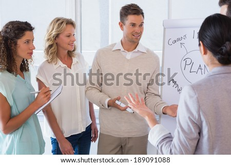Casual businessman giving presentation to colleagues in the office - stock photo