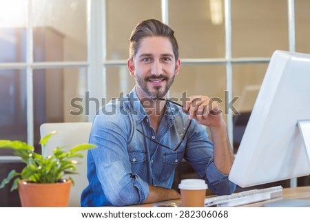 Casual businessman holding glasses and smiling at camera in the office