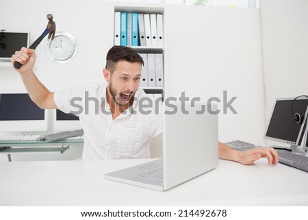 Casual businessman holding hammer over laptop in his office