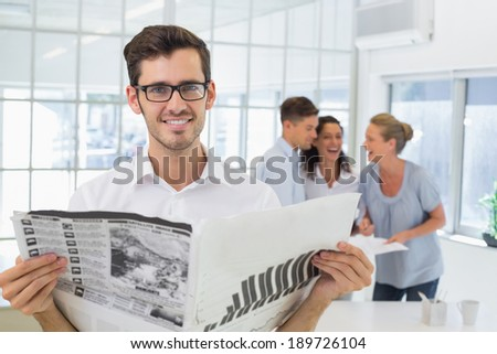 Casual businessman holding newspaper smiling at camera in the office - stock photo