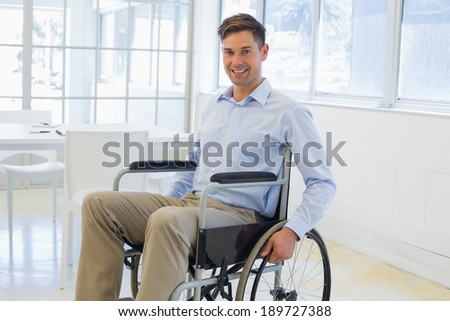 Casual businessman in wheelchair smiling at camera in the office - stock photo