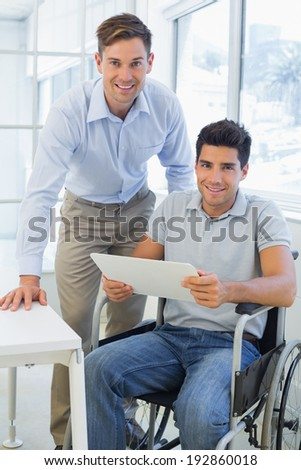 Casual businessman in wheelchair smiling at camera with colleague in the office - stock photo
