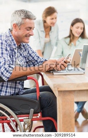 Casual businessman in wheelchair using smartphone in the office - stock photo