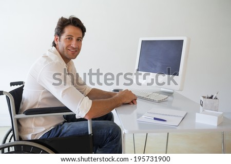 Casual businessman in wheelchair working at his desk in his office - stock photo