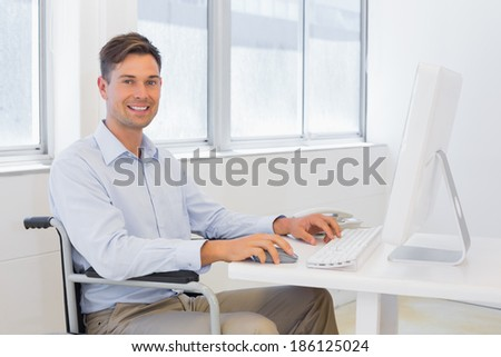 Casual businessman in wheelchair working at his desk in the office - stock photo