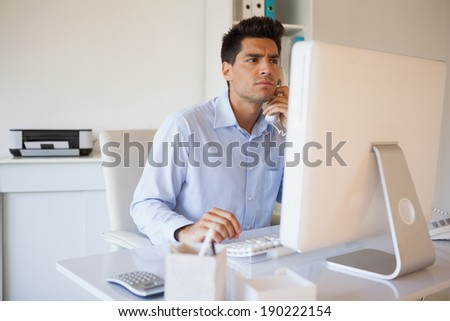 Casual businessman on the telephone at desk in his office