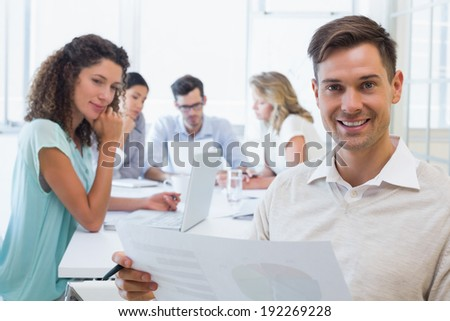 Casual businessman reading document during meeting in the office