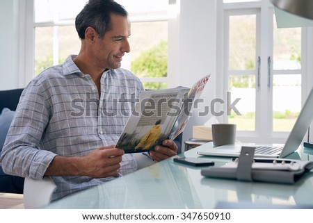 Casual businessman seated at home office space reading business magazine smiling - stock photo