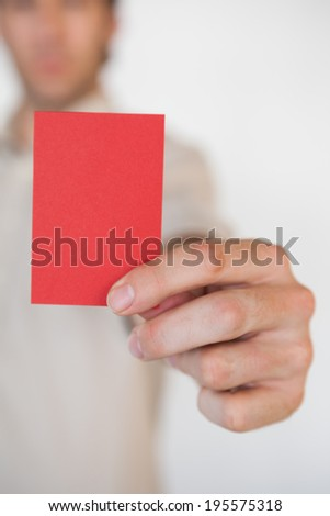 Casual businessman showing red card in the office - stock photo