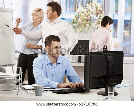 Casual businessman sitting at office desk, working on computer. Businesspeople working in background.? - stock photo