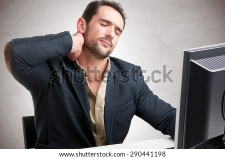 Casual businessman sitting in a desk with pain in his neck - stock photo