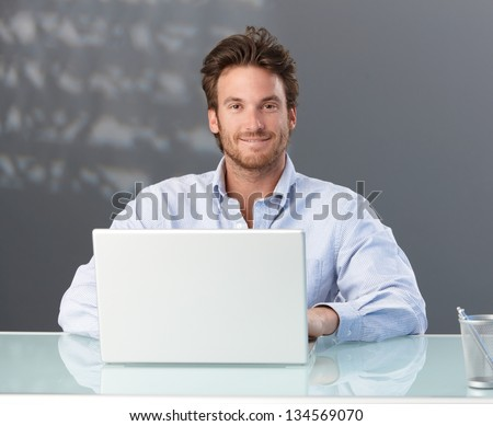 Casual businessman sitting in office with laptop computer, smiling at camera. - stock photo