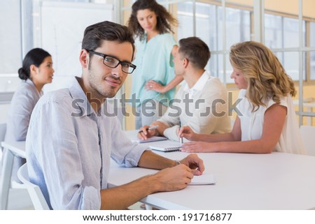 Casual businessman smiling at camera during meeting in the office