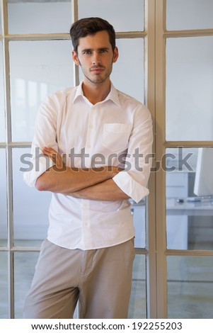 Casual businessman standing with arms crossed in his office