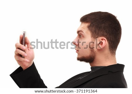Casual businessman surprisedly looking at his phone screen isolated on white - stock photo