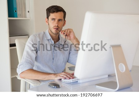 Casual businessman thinking at his desk in his office