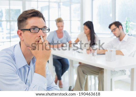 Casual businessman thinking with team behind him in the office - stock photo