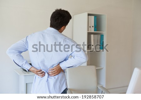 Casual businessman touching his sore back in his office