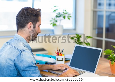 Casual businessman typing on laptop in the office - stock photo