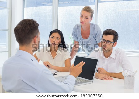 Casual businessman using his laptop during a meeting in the office - stock photo