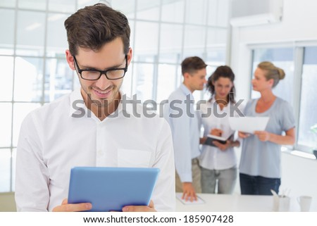 Casual businessman using his tablet in the office - stock photo