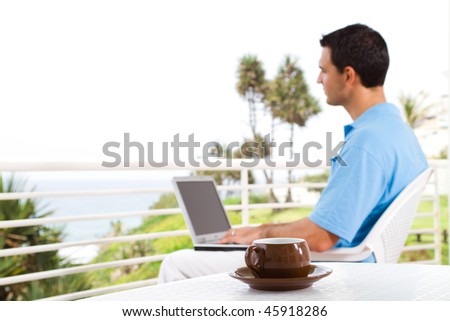 casual businessman using laptop on balcony with sea view behind, shallow focus on the coffee cup