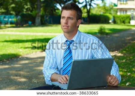 Casual businessman using laptopn in park summertime. - stock photo