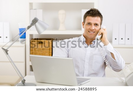 Casual businessman working at home using laptop computer, talking on phone. - stock photo