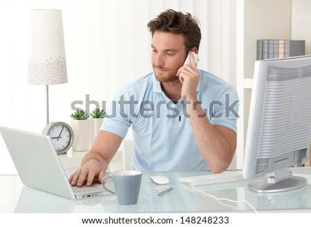Casual businessman working at office desk, using mobile phone and laptop computer, typing, making phone call, smiling.