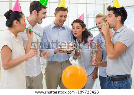 Casual businessmen team celebrating a birthday in the office - stock photo