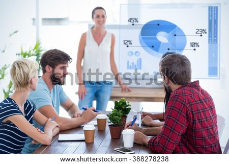 Casual businesswoman giving presentation to her colleagues against global business interface - stock photo