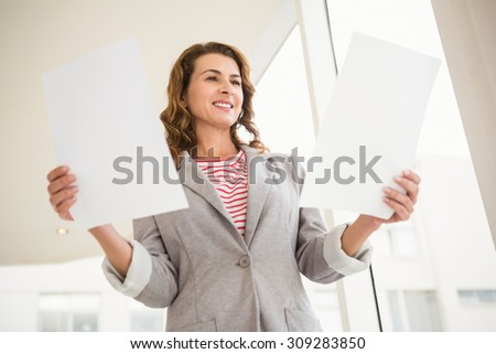 Casual businesswoman holding papers in the office