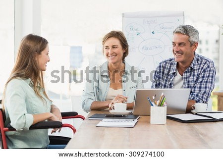 Casual businesswoman in wheelchair talking to colleagues in the office - stock photo