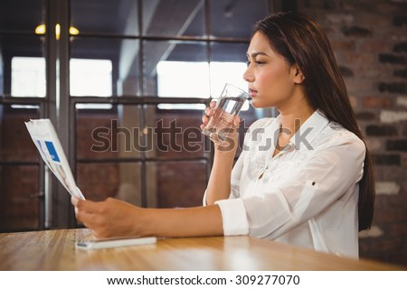 Casual businesswoman looking at files in a cafe - stock photo