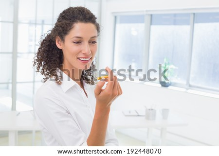 Casual businesswoman looking at her electronic cigarette in the office - stock photo