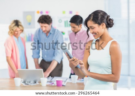 Casual businesswoman using digital tablet with colleagues behind in the office - stock photo