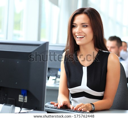Casual businesswoman using laptop in office, sitting at desk, typing on keyboard