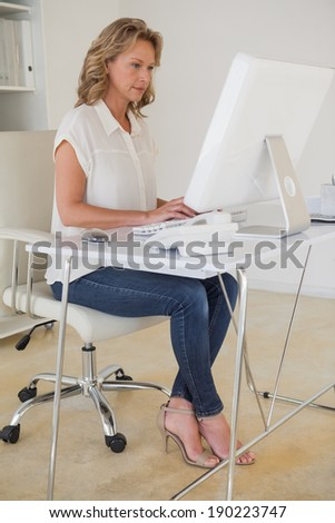 Casual businesswoman working at her desk in her office
