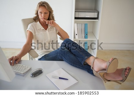 Casual businesswoman working with her feet up at desk in her office