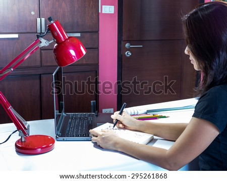Casual businesswoman writing on notebook with laptop computer in modern office - stock photo