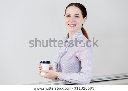 Casual caucasian woman standing at balcony with coffee in hands