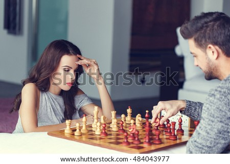 Casual caucasian woman thinking during chess game indoor