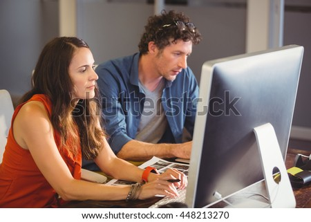 Casual colleagues using computer in the office - stock photo