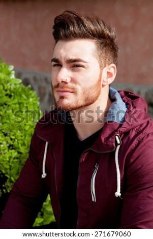 Casual cool young man with beard in the park - stock photo